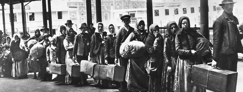 Immigrants on line leaving Ellis Island waiting for ferry to N.Y